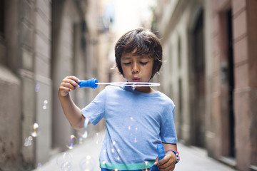 Little boy blowing soap bubbles in the street