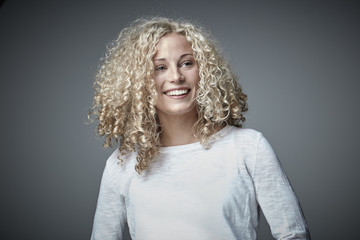 Portrait of happy blond woman with curly hair