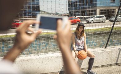 Young man taking photo of young woman at basketball court