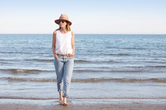 Enjoying summer. Beautiful woman walking on beach in casual.