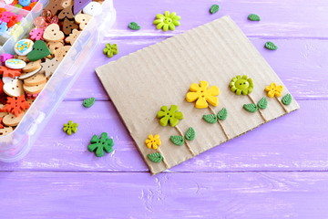Fun card with flowers. Flowers buttons and leaves on lilac wooden background. Plastic box with colorful buttons. Make kids crafts from recycled materials: cardboard and buttons