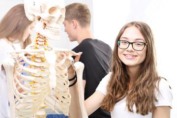 Uczennica ogląda model ludzkiego szkieletu.