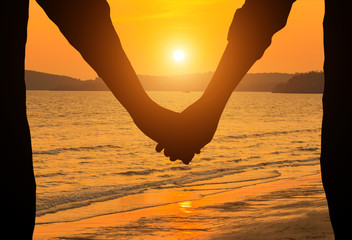 silhouette couple holding hands on the beach in sunset