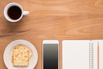 Mobile phone, notebook, pencil, coffee, tea, food cracker