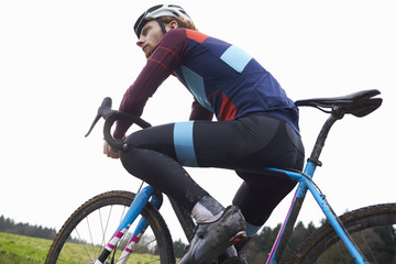 Male cyclist pauses on bike in open countryside, low angle