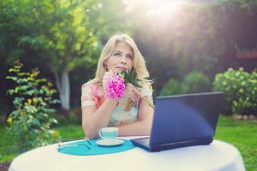 Красивая блондинка за чашкой кофе и ноутбуком в саду