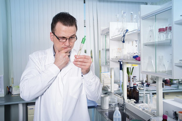 Lab worker in glasses observing test tube with mold at the laboratory