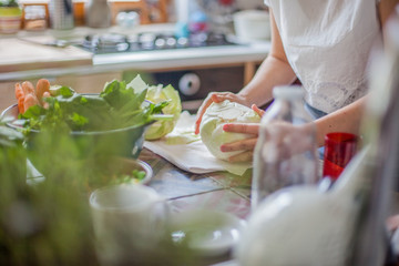 Woman cooking in kitchen with ingredients around her