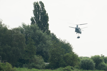 Chinook helicopter carying a load over a forest