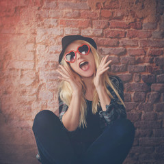 Happy Fashion Girl in Style with Glasses on Brick Wall