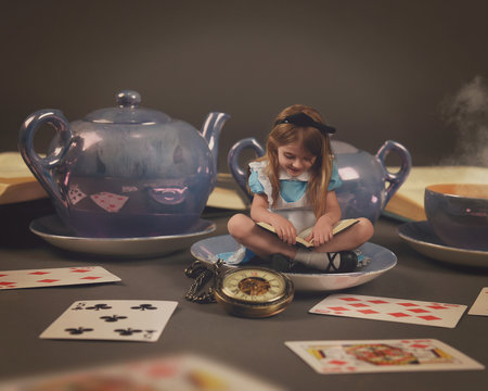 Little Girl Reading Fairy Tale Book with Teacup