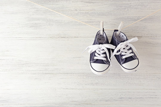 Baby sport shoes hanging on the clothesline on light wooden background