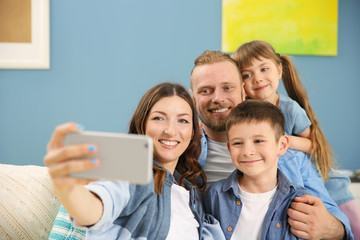 Happy family taking selfie on blue wall background