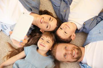 Happy family taking selfie on the floor