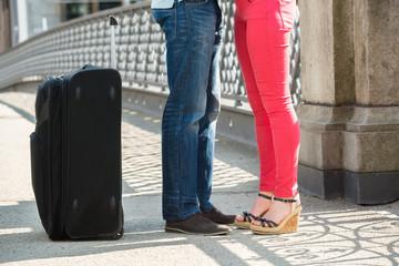 Couple Standing On Bridge With Luggage