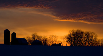 Silhouette of farm and tree in snow at sunset