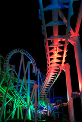Modern rollercoaster lit up with different colors of light at night.
