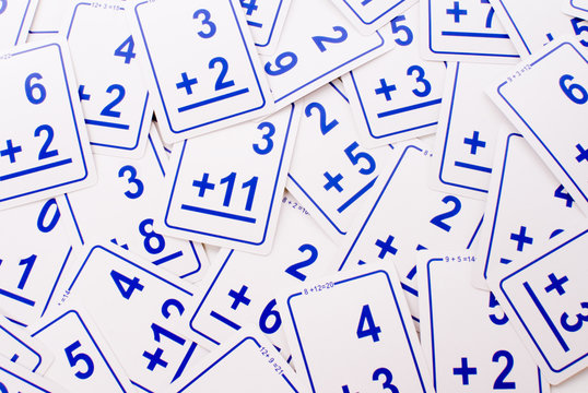 Education: Blue addition math cards  randomly spread out on table. Educational school supplies. Edicational background