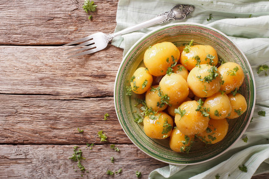 Glazed new potatoes with parsley close-up on the table. horizontal top view