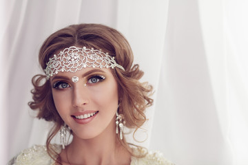 Studio portrait of beautiful bride with perfect hairstyle and ma
