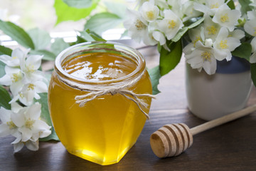 Delicious fresh spring honey in glass jar, wooden spoon and blooming branch and flowers of jasmine in white-blue ceramic cap on black stone board against  background of window
