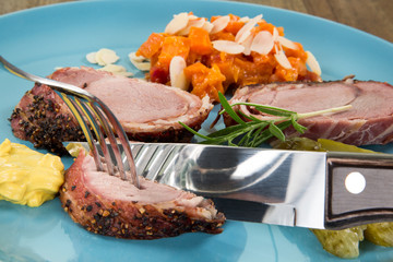 Schweinefilet und Karottengemüse, auf blauem Teller mit Spiegelung angerichtet. Fleisch wird mit Bestek geschnitten.