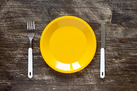 Empty yellow plate, fork and knife