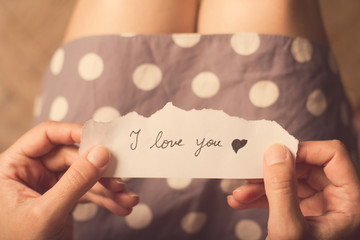 Woman holding a paper note with the text I love you