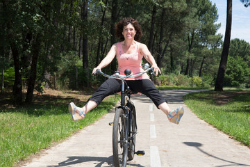 Happy woman having fun riding her bike in summer