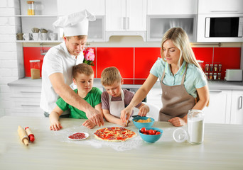 Happy family making pizza in kitchen