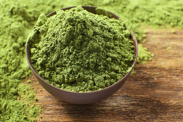 Powdered matcha green tea on wooden table