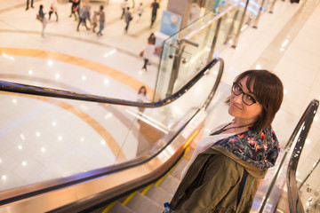 smiling woman rides on the escalator