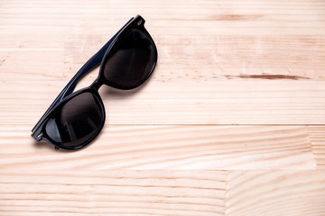 Sunglasses in a top left corner on a light wooden background. La