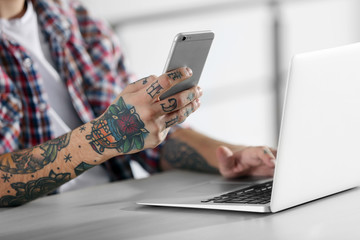 Young man with tattoo using laptop and mobile phone at the table
