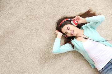 Beautiful girl with headphones lying on floor