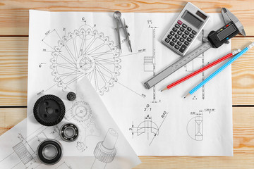 Engineering drawings of parts with tools on wooden table