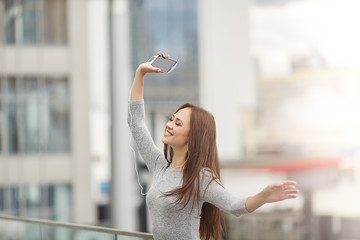 Beautiful young woman holding a phone with headphones and dancing with eyes closed.