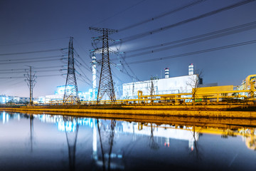 buildings of modern power station near river at twilight