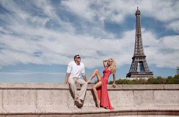Beautiful young blondie sexy female model in a long red dress sitting with a handsome tall man in a white T-shirt and pants on the wall in Paris, France with the Eiffel Tower