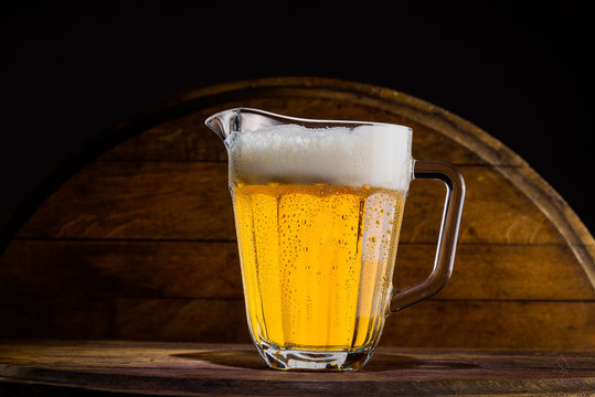 Pitcher of beer on wooden background