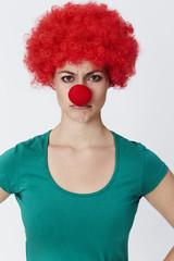 Annoyed clown in red wig, portrait
