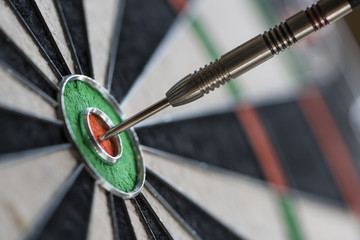 Single dart hitting bull's eye on the dartboard