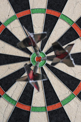 Darts hitting bull's eye on the dartboard