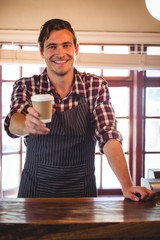 Portrait of waiter offering a cup of coffee