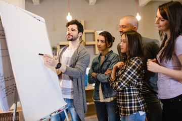 Team of graphic designer discussing chart on white board
