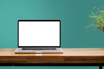 laptop on wooden desk with green wall background