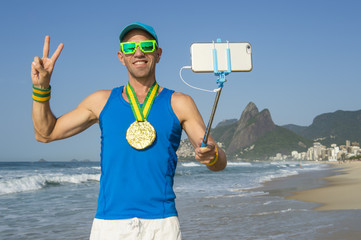Athlete with gold medal posing for a celebratory selfie at Ipanema Beach, Rio de Janeiro, Brazil