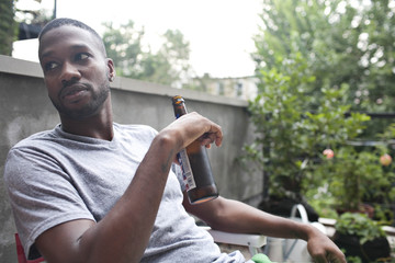 Man drinking beer while sitting outdoors