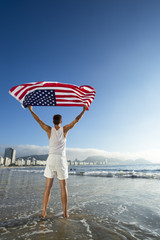 Athlete in white outfit standing with American flag waving in the wind on the shore of Copacabana Beach, Rio de Janeiro, Brazil