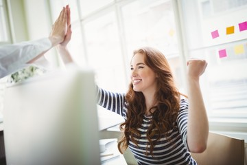 Excited coworkers giving high-five at creative office